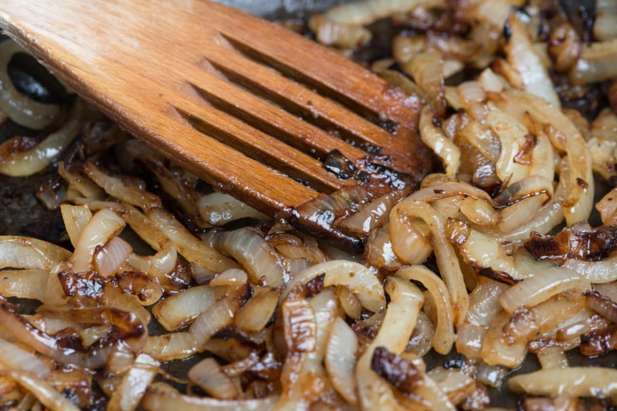 caramelized onions with a wooden spatula cooking in a skillet