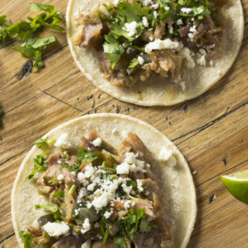Tortillas topped with Mexican pulled pork, cilantro, and cotija cheese for Mexican Carnitas