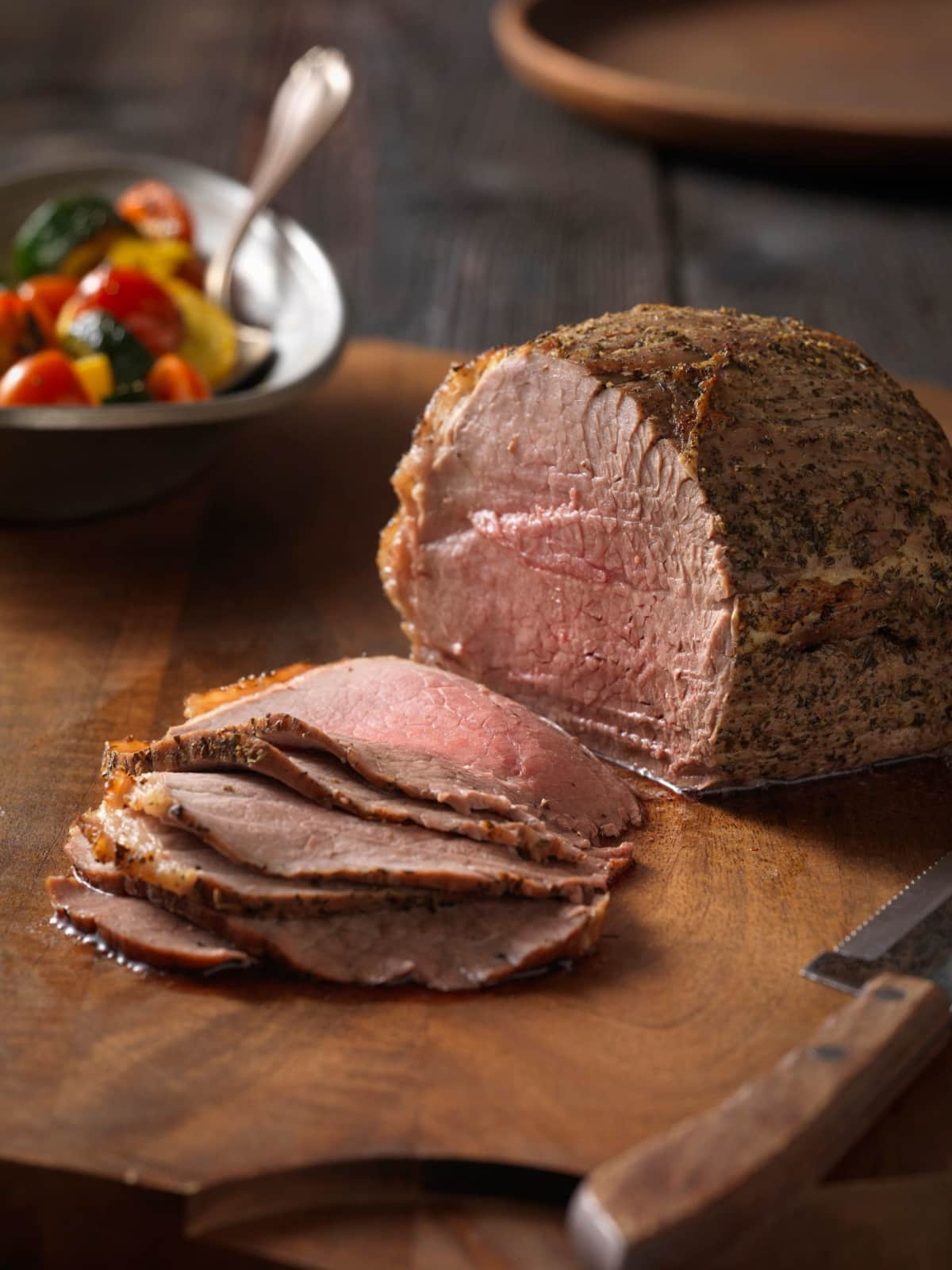 Carved top round roast on a wooden board with a bowl of mixed vegetables in the background.