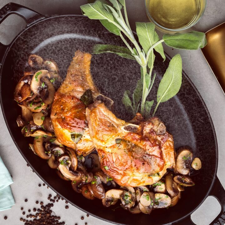 Cast Iron Skillet Pork Chops with sage, peppercorns, and sauteéd mushrooms on the side.