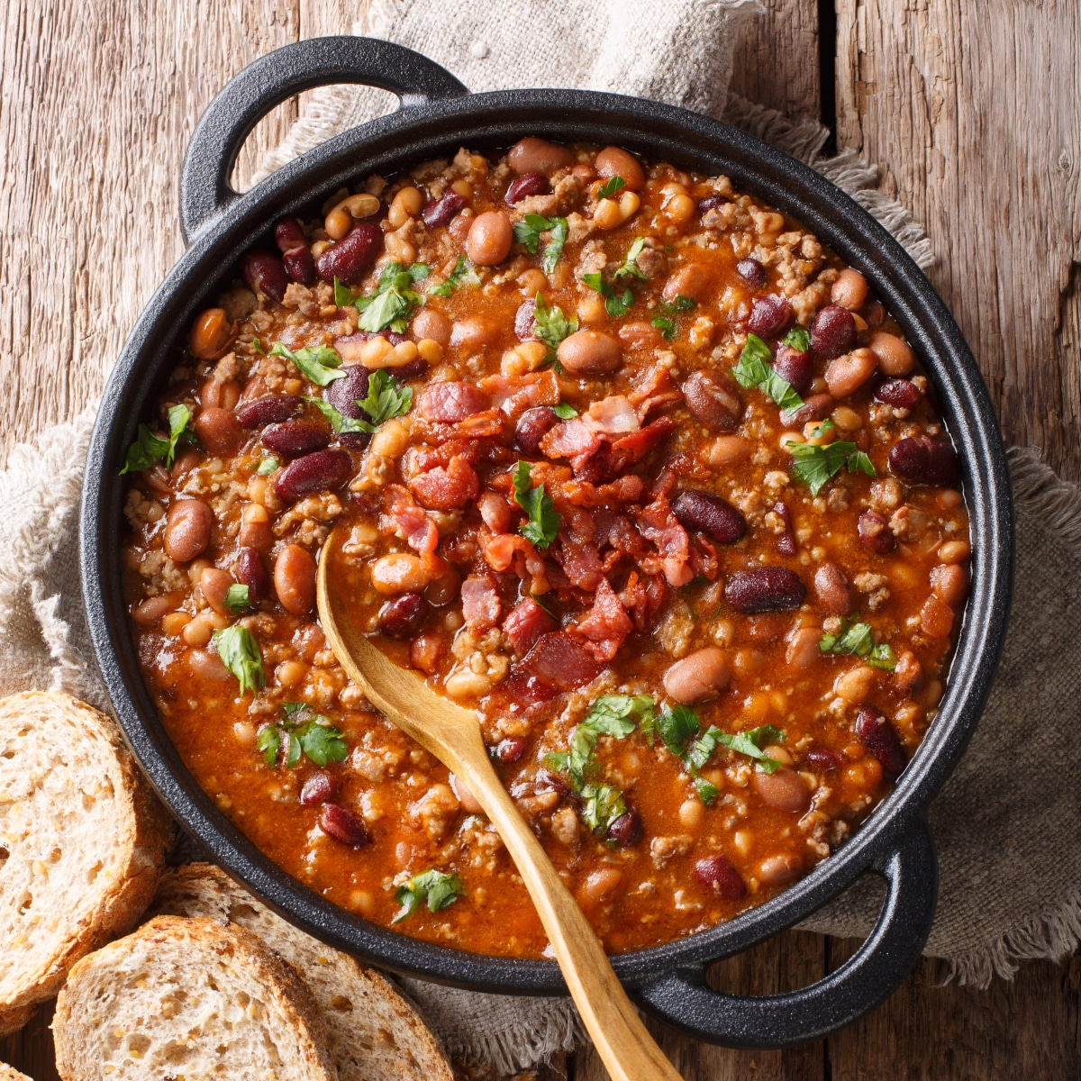 overhead view of Mexican Cowboy Beans with tomatoes, pinto beans, chorizo, and cilantro