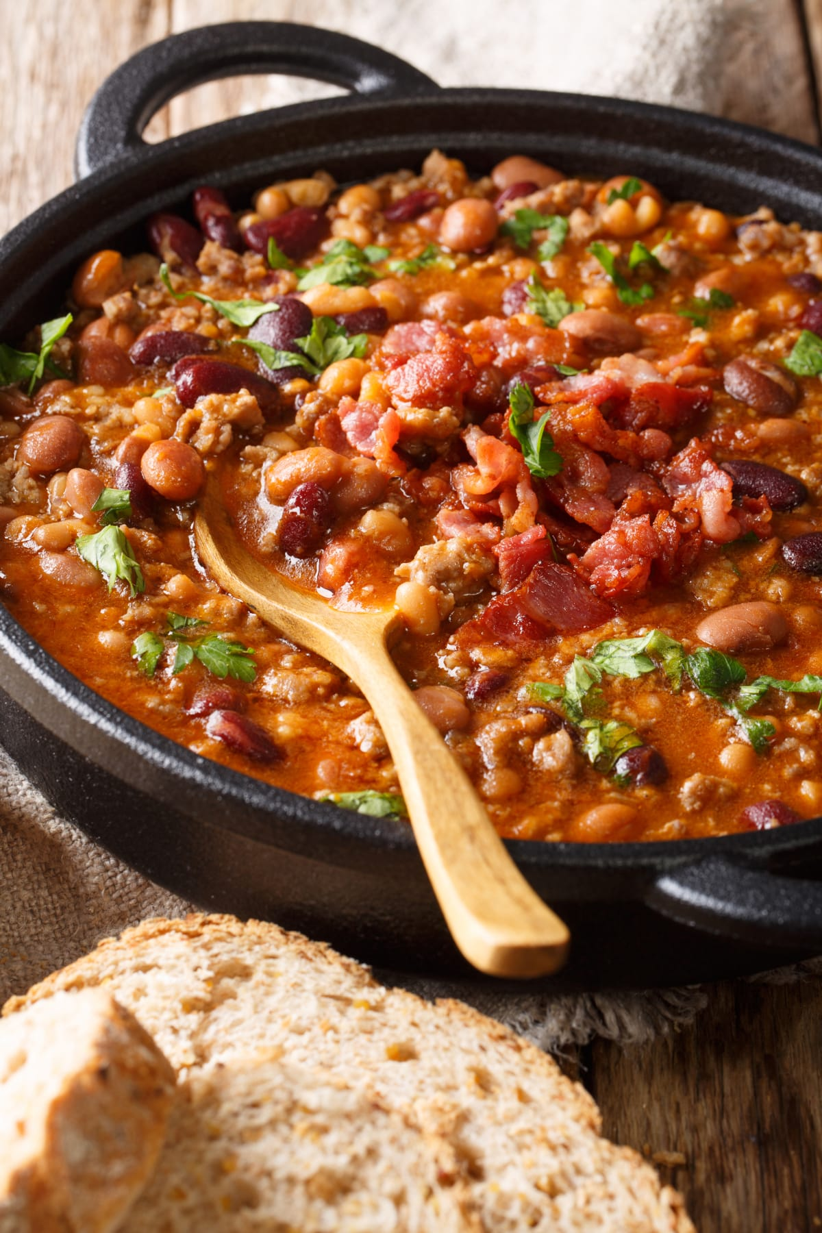 large dish with beans, tomatoes, chorizo, and cilantro and wooden spoon