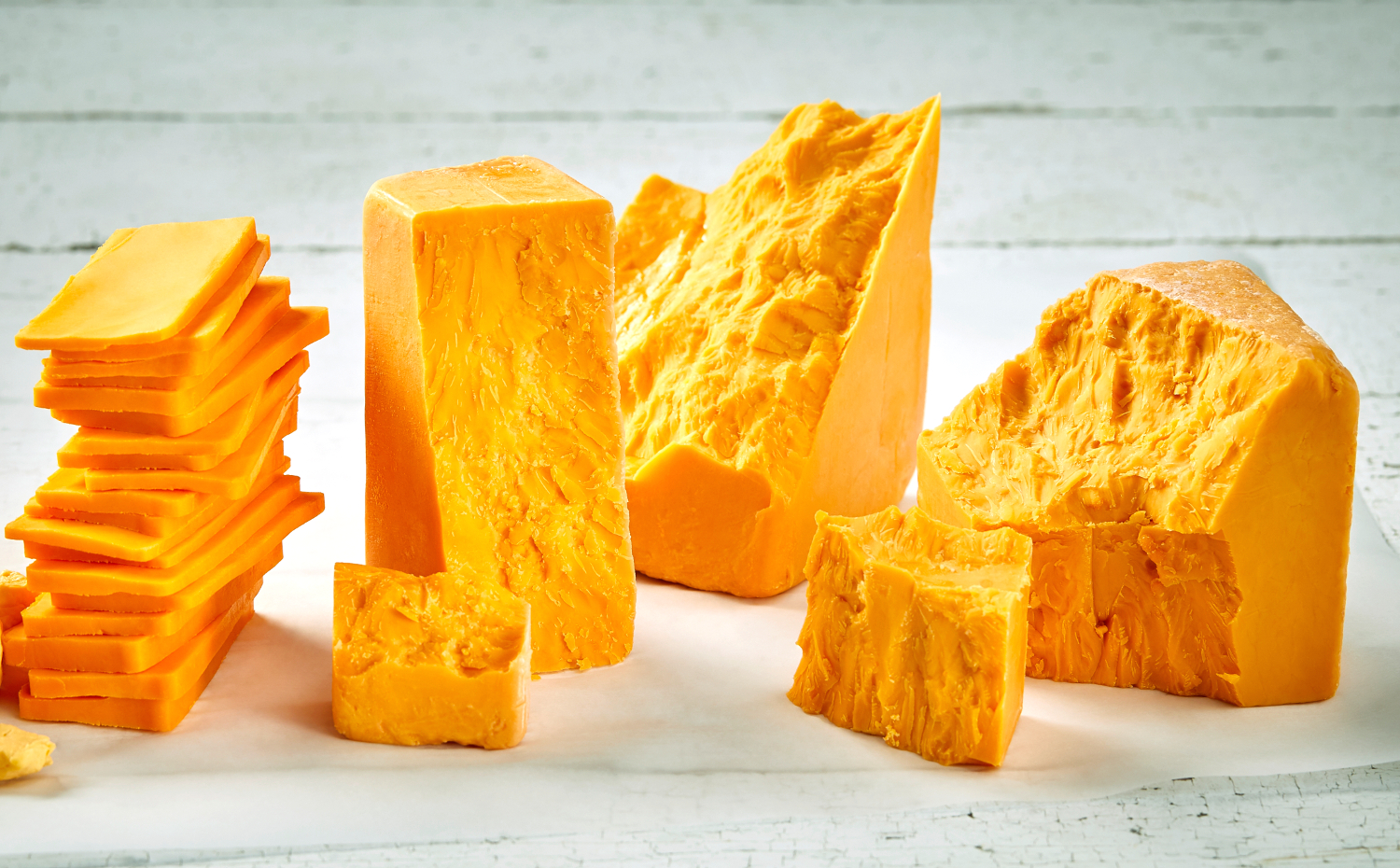 Assortment of cheddar cheese with blocks of various ages and slices