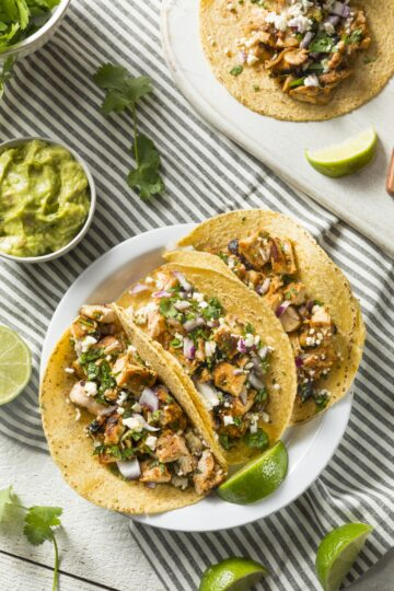 Chicken Tinga Tacos viewed from the top down. 3 tacos are assemble and on a plate. Guacamole and limes are served as garnishes on the side.