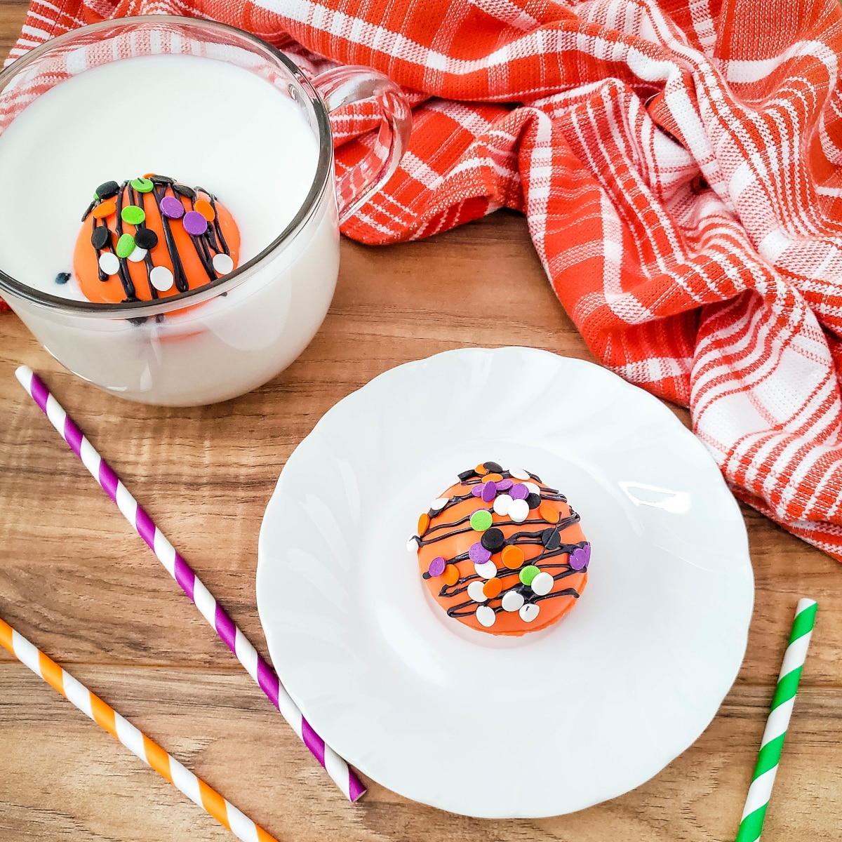 top down view or orange and black decorated cocoa bombs for Halloween. One bomb is on a plate and the other is in a mug of warm milk.