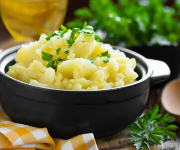 Closeup of creamy mashed potatoes made with cream cheese and chives. Ready to serve.