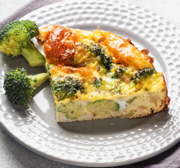 Crustless Quiche slice on plate with broccoli