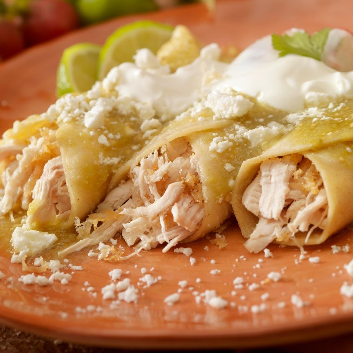 Enchiladas Verdes - Green Enchiladas. Chicken Enchiladas with green sauce. Served on a stoneware plate. Enchiladas are sprinkled with crumbled cotija cheese.