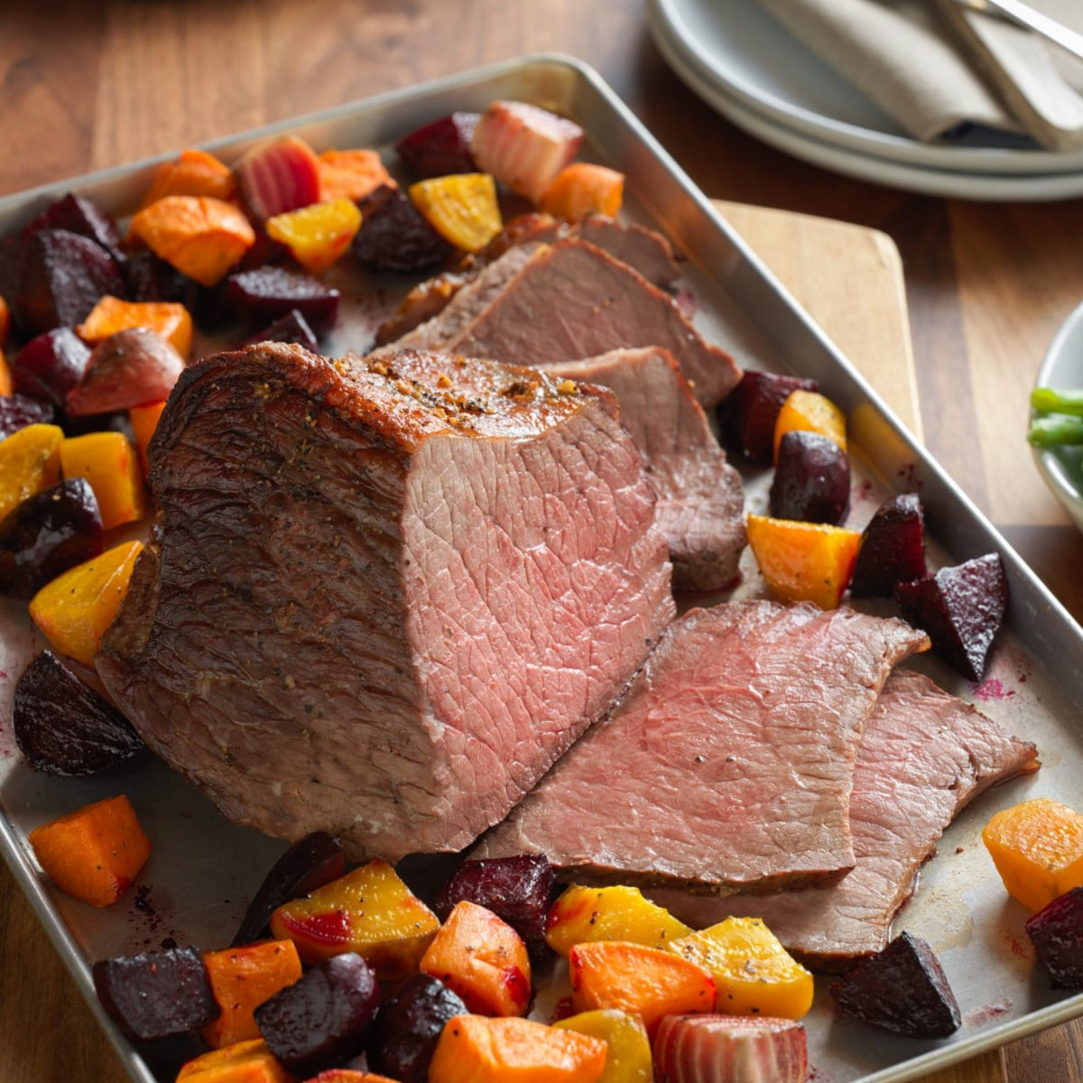 Eye of round roast beef on a tray with root vegetables