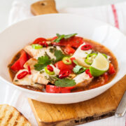 Fish stew with chunks of white fish, tomatoes, herbs, chili peppers, lime.