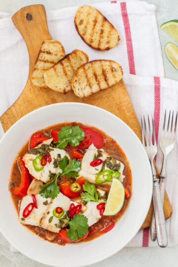 Fish stew with chunks of white fish, tomatoes, herbs, chili peppers, lime served with crusty bread.