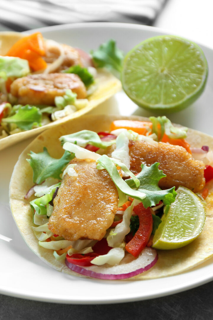 Fish Tacos with sauce served with cabbage slaw and limes on flour tortillas