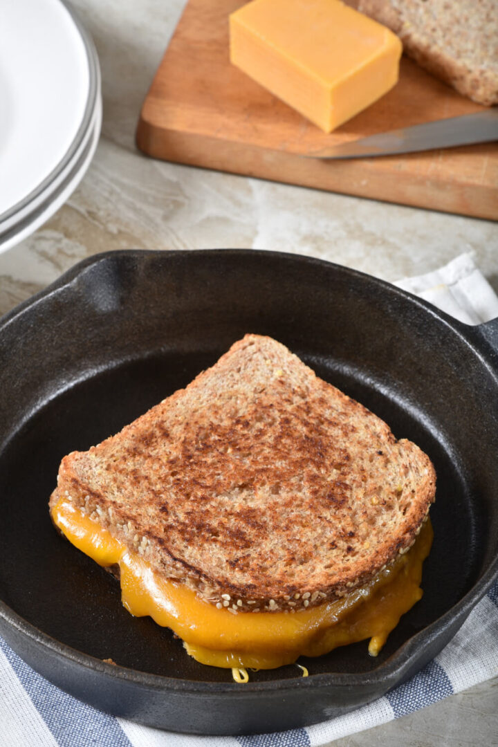 Grilled cheese in skillet with block of cheddar. Sandwich is grilled and ready to cut and serve.
