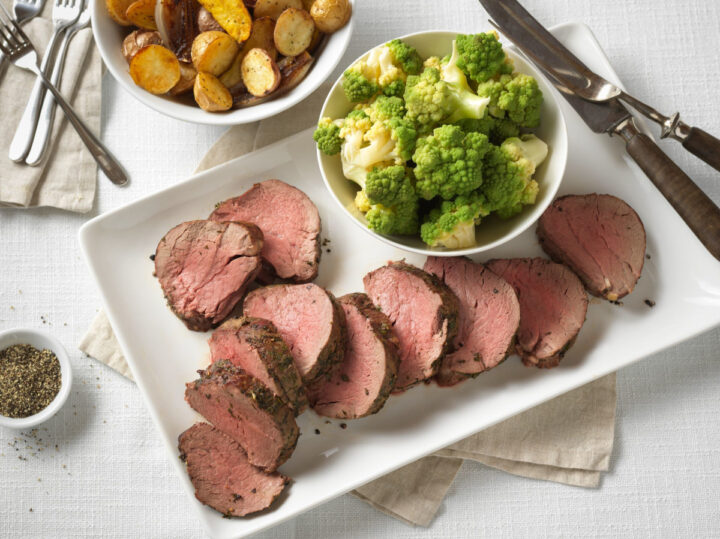Top round roast sliced on a white platter served with a side of broccoli and roasted potatoes. Top down view.