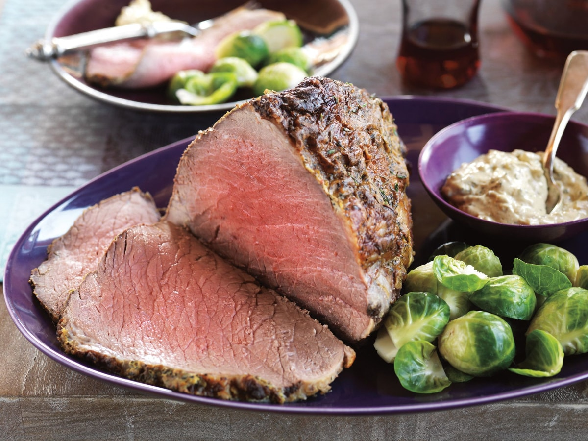 eye of round roast beef recipe with brussels sprouts and horseradish sauce on the side served on a purple platter