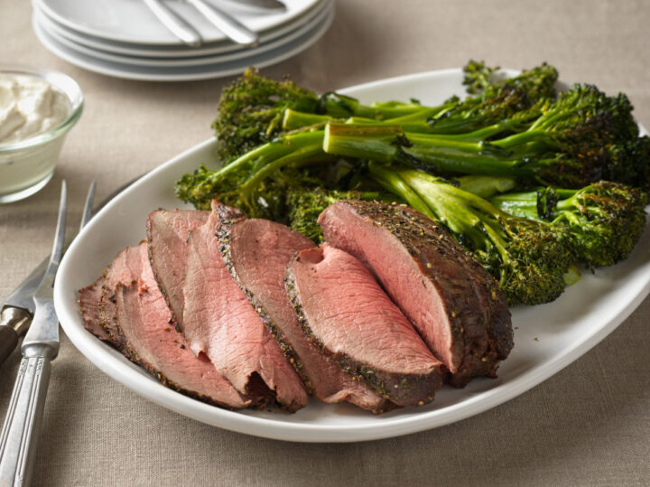 top round roast carve on a white serving platter with broccolini served alongside