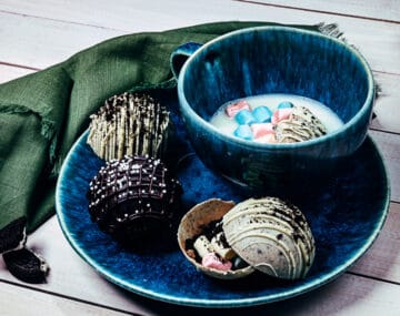 Hot chocolate bomb melting in cup, one chocolate bomb open on the side, two decorated hot chocolate bombs on the side.