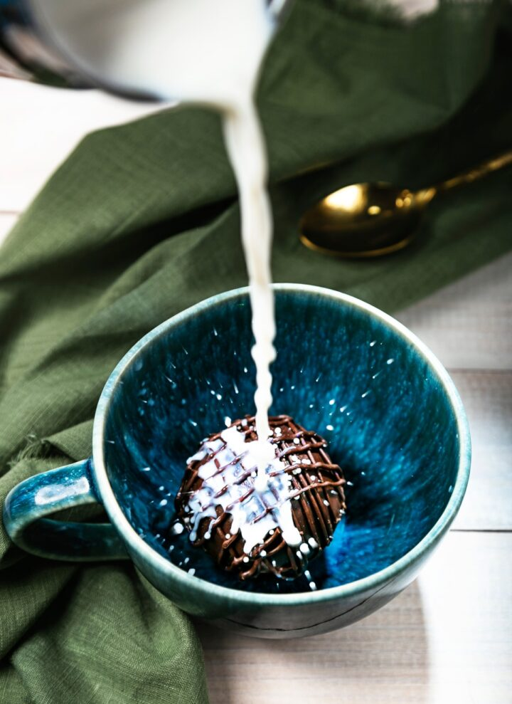 Hot chocolate bomb with warm milk pouring over it in a blue cup.