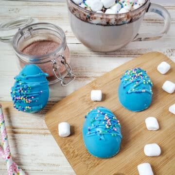 3 Easter blue chocolate bombs eggs sitting on a board with the hot chocolate bomb melted in a mug in the back.