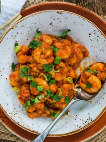 Spicy Hunan Shrimp served on pottery plate with speckles.