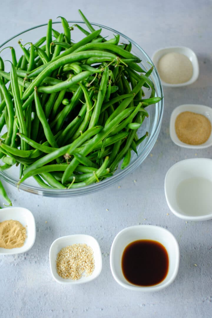 Ingredients to toss with air fryer green beans. Ingredients are measure out in bowls on a working surface. The view is from top down.