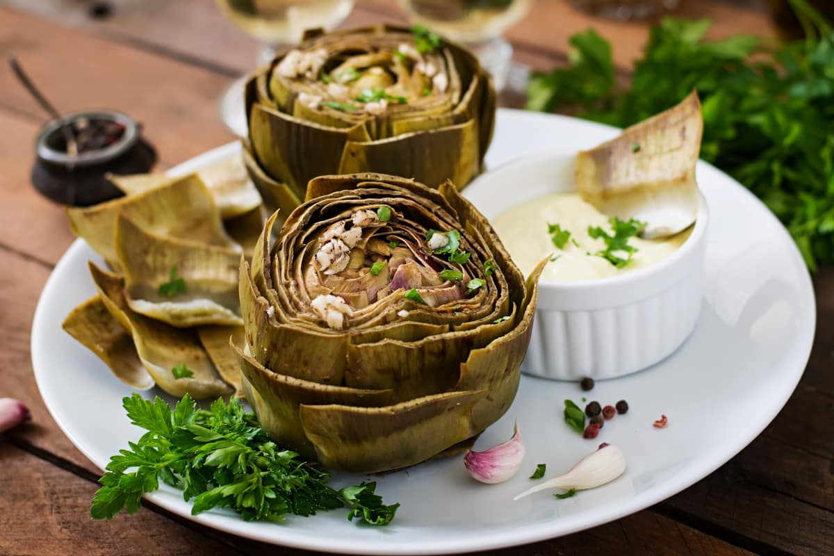 2 Instant Pot Artichokes served with dipping sauce shown from a 45 degree angle.