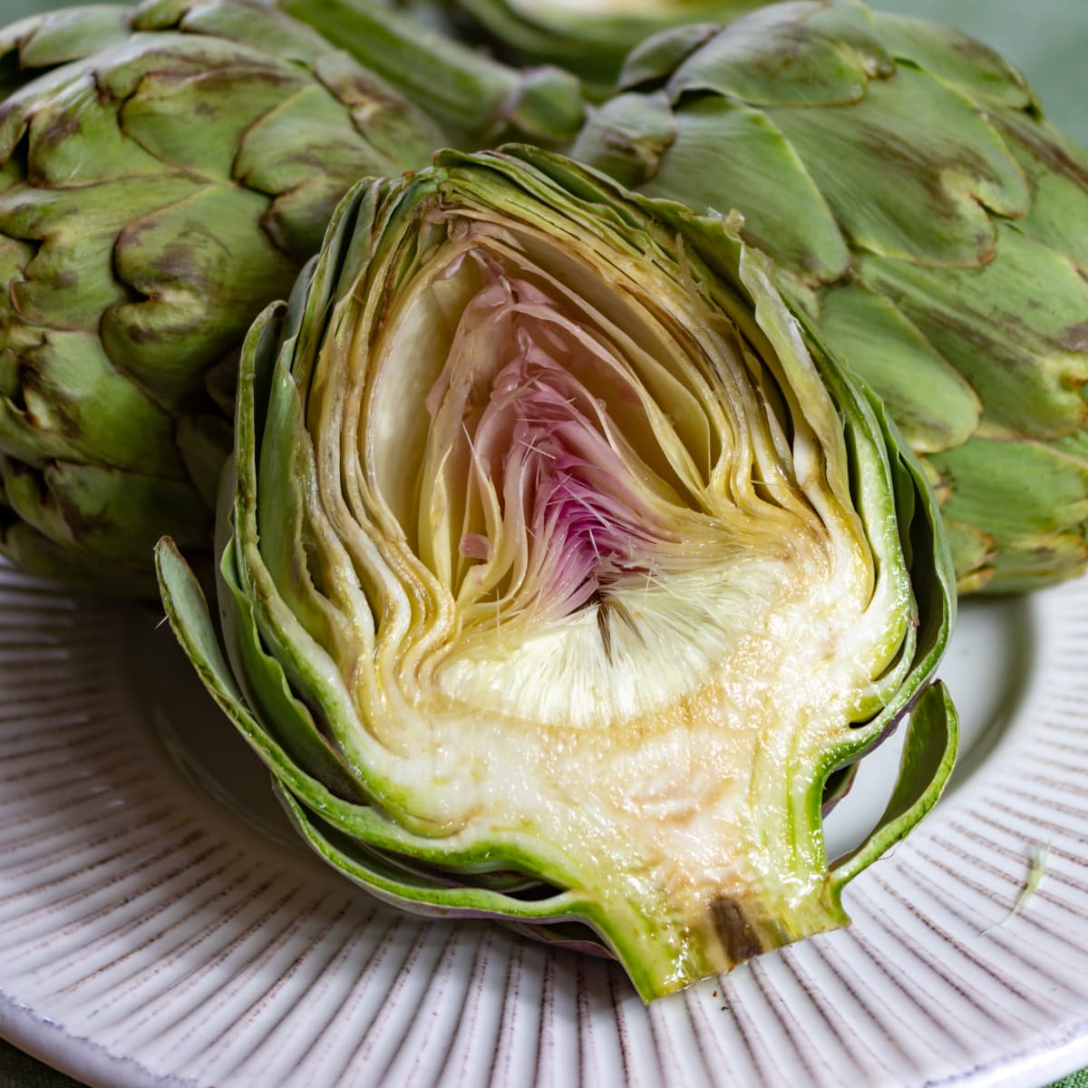 Artichoke Cross Section Showing Bracts, Choke and Heart on a plate with 2 whole artichokes