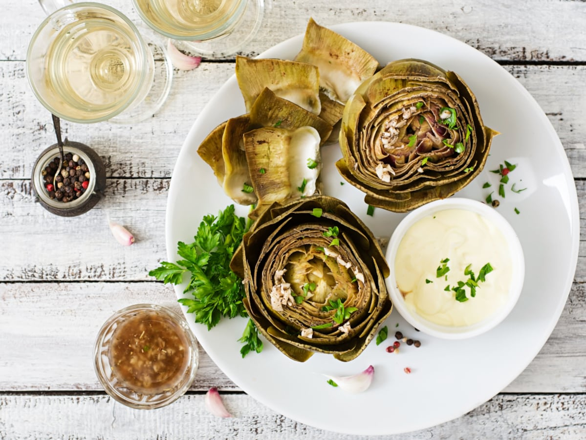 Instant Pot Artichokes trimmed and serve with dipping sauces and white wine. Top down view on a white plate and rustic white board