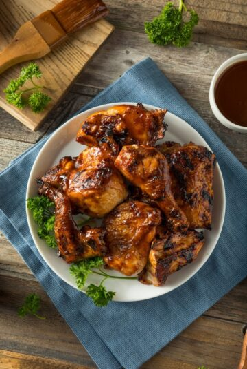 Instant Pot BBQ Chicken ready to eat. Served with extra BBQ sauce on the side and garnished with herbs