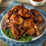 Mouthwatering Instant Pot BBQ Chicken plated with a bowl of bbq sauce on the side