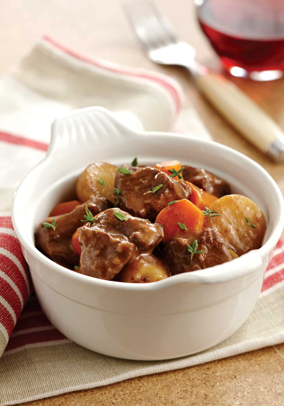 Instant Pot Beef Stew served in a white ceramic bowl on a red and white cloth