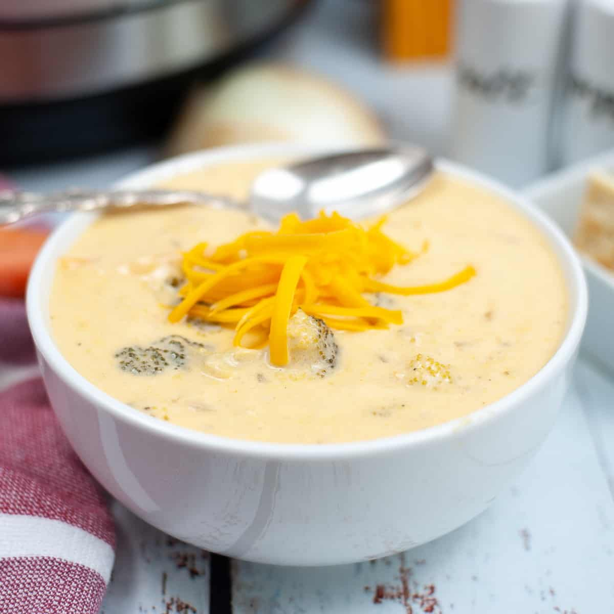 closeup of a bowl of Instant Pot broccoli cheddar soup garnished with some shredded cheddar cheese