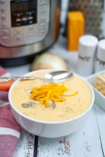 instant pot broccoli cheddar soup garnished with additional cheddar is served in a white bowl with a spoon on top. The Instant Pot and some of the ingredients are in the background.