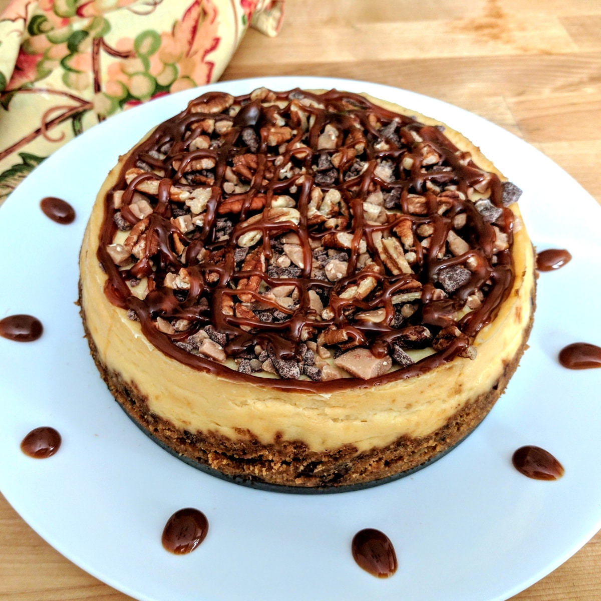 Instant Pot Cheesecake with toffee, chocolate, caramel and pecans on a white plate.