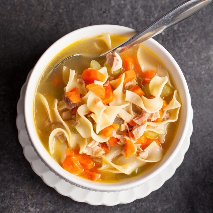 Instant Pot Chicken Noodle Soup with chicken thighs, carrots, onions, celery, and wide eggs noodles for the perfect comfort food bowl of soup.