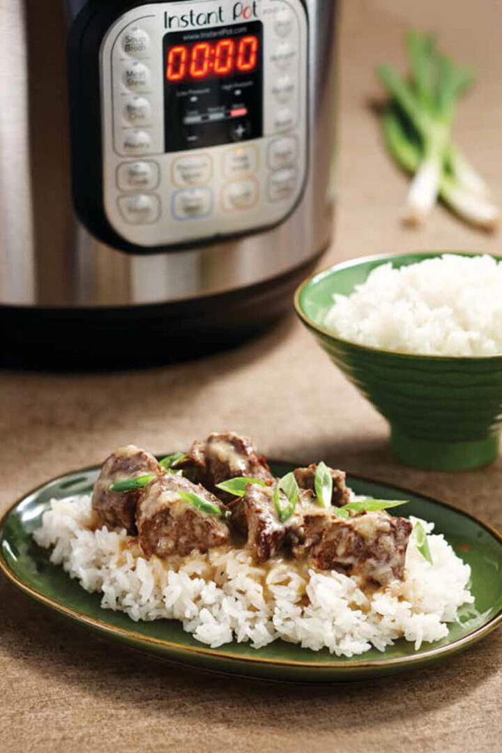 Instant Pot in background with beef curry and jasmine rice