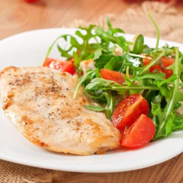 Instant Pot Frozen Chicken breasts cooked and served on a plate with a side salad.