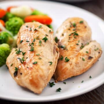 2 cooked Instant Pot frozen chicken breasts served on a white plate shown closeup.