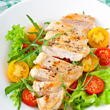 Sliced cooked Instant Pot frozen chicken breasts sliced and served on top of a green salad with sliced yellow and red tomatoes.