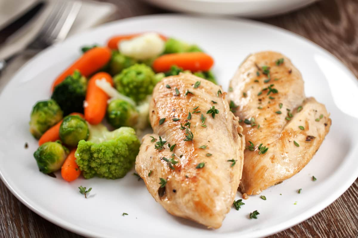 2 cooked Instant Pot frozen chicken breasts served on a white plate with a side of vegetables.