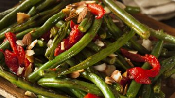 Green Beans with Pimentos and chopped almonds. This variation of the recipe shows a slight char on the beans and pimentos.