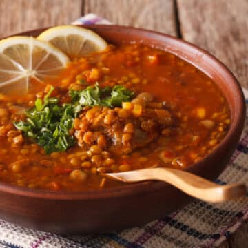 Instant Pot lentils soup with lemon slices and parsley garnishes in a serving bowl. Wooden spoon in bowl shows the creamy and textured consistency for the soup.