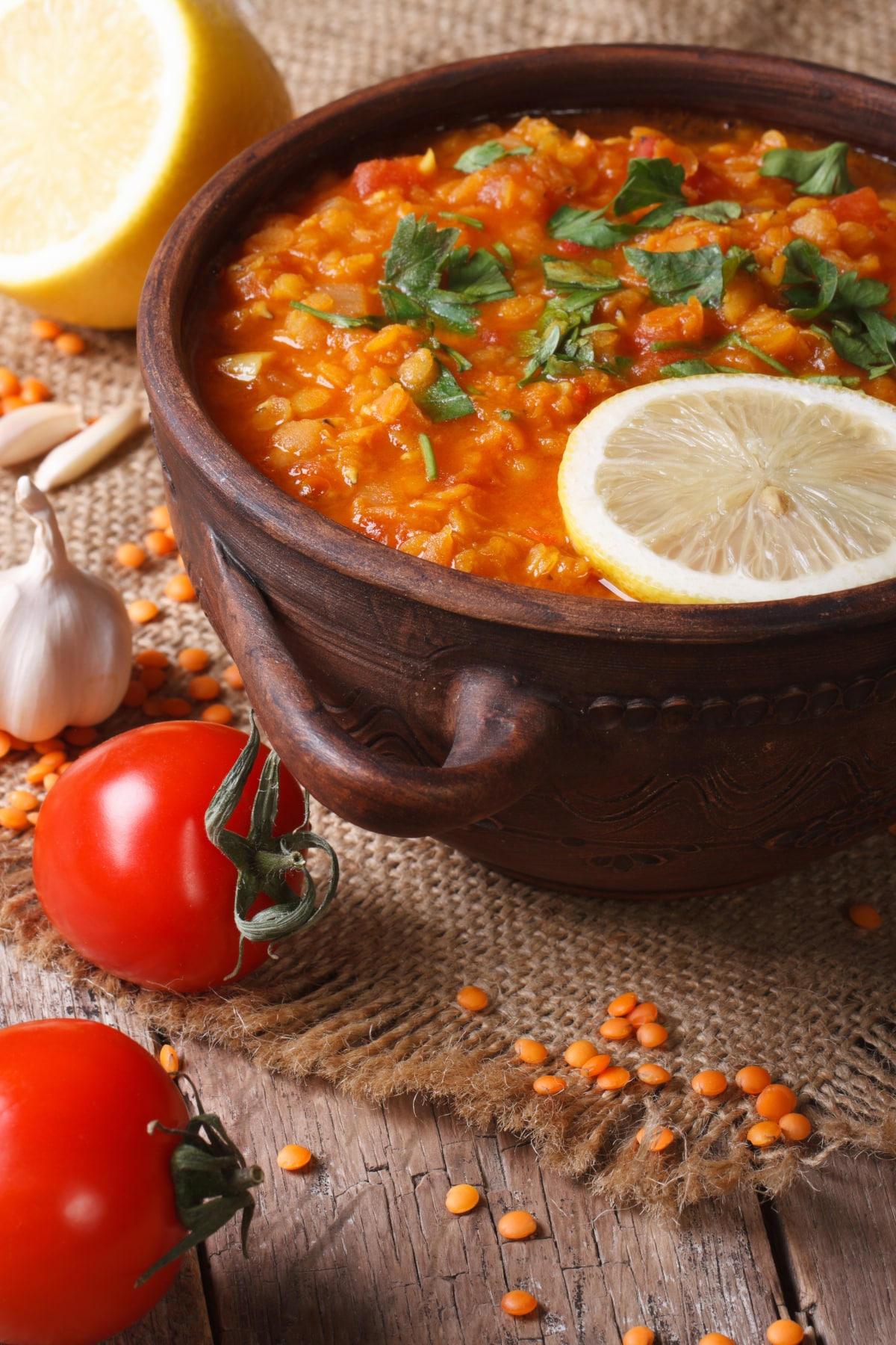 instant pot lentils soup with Moroccan spices in a rustic pot garnished with lemon and parsley.