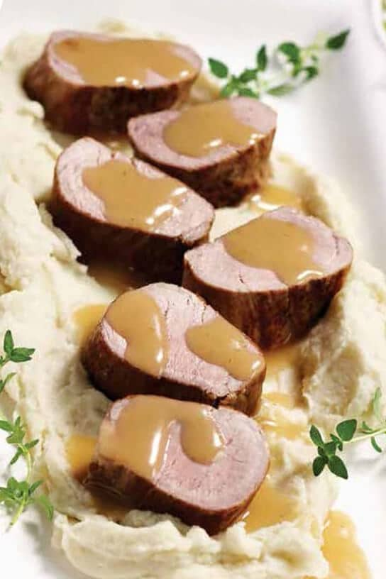 Instant Pot Pork Tenderloin on a bed of creamy mashed potatoes with maple dijon gravy drizzle over the top.