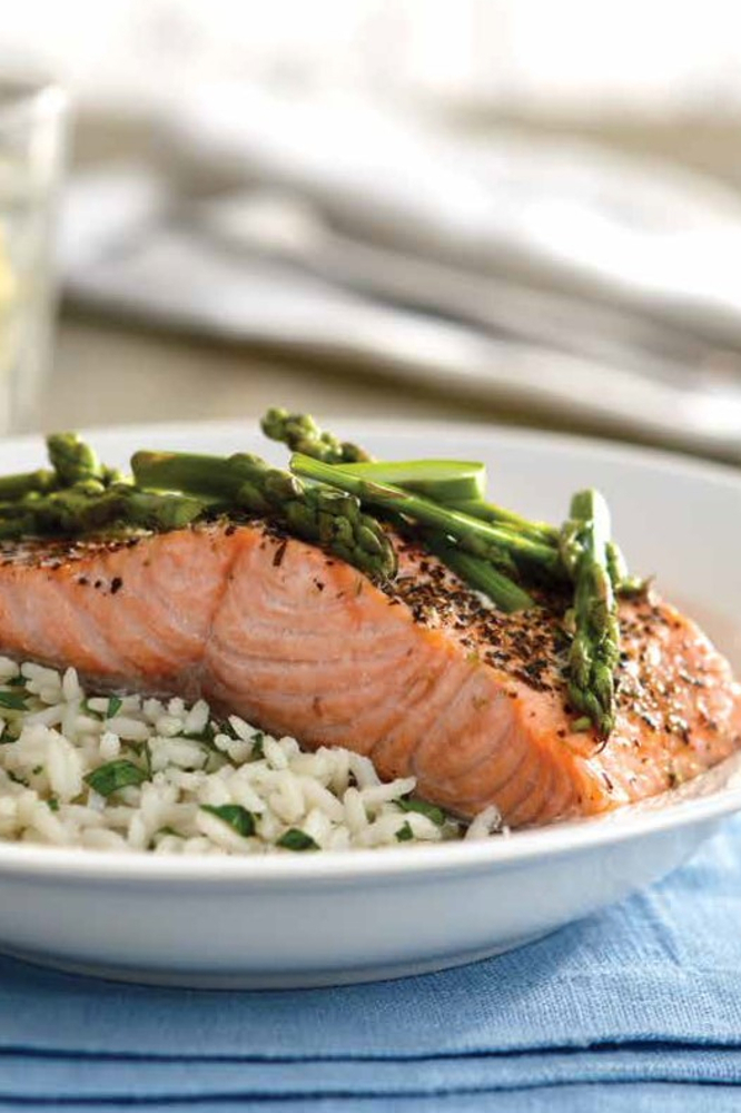 Salmon with herbs and asparagus served on rice pilaf