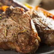 grilled lamb chops served with roasted carrots on a plate
