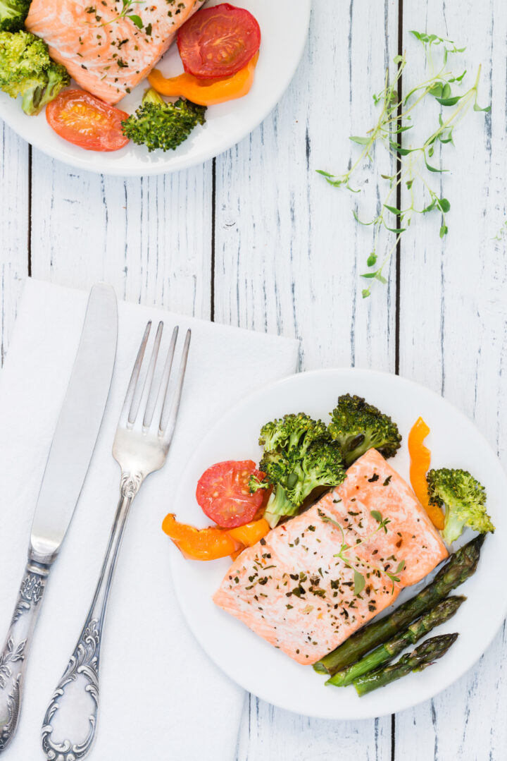 Oven baked salmon served with lightly roasted broccoli, asparagus and tomatoes.
