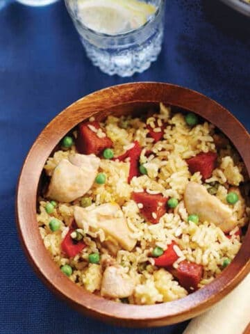 Paella recipe with chicken, seafood, rice and vegetables served in a bowl.