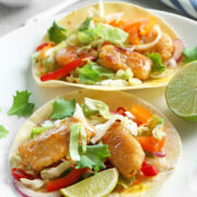 Fish Tacos with Sauce, coleslaw mix, onions and lime.