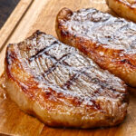 two cooked picanha steaks on a carving board ready to be served